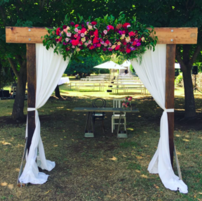 Dark timber 3 post arch with draping and florals